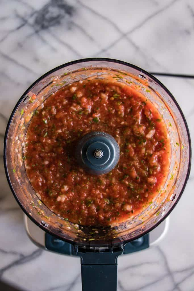 Food processor filled with just processed homemade salsa.
