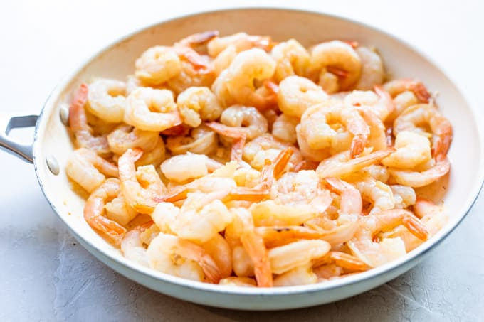 Skillet full of cooked shrimp.