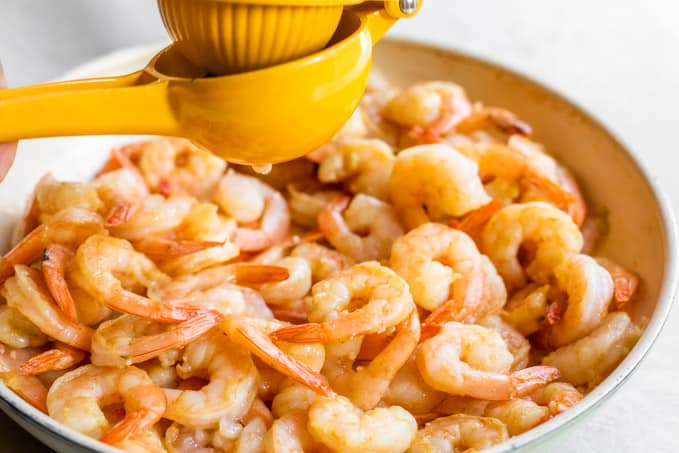Squeezing lime juice over cooked shrimp.