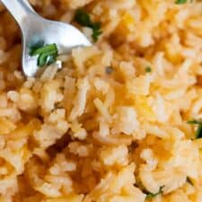 Close up view of Mexican Rice or Arroz Rojo, showing the fluffy texture and pale red color of the rice.