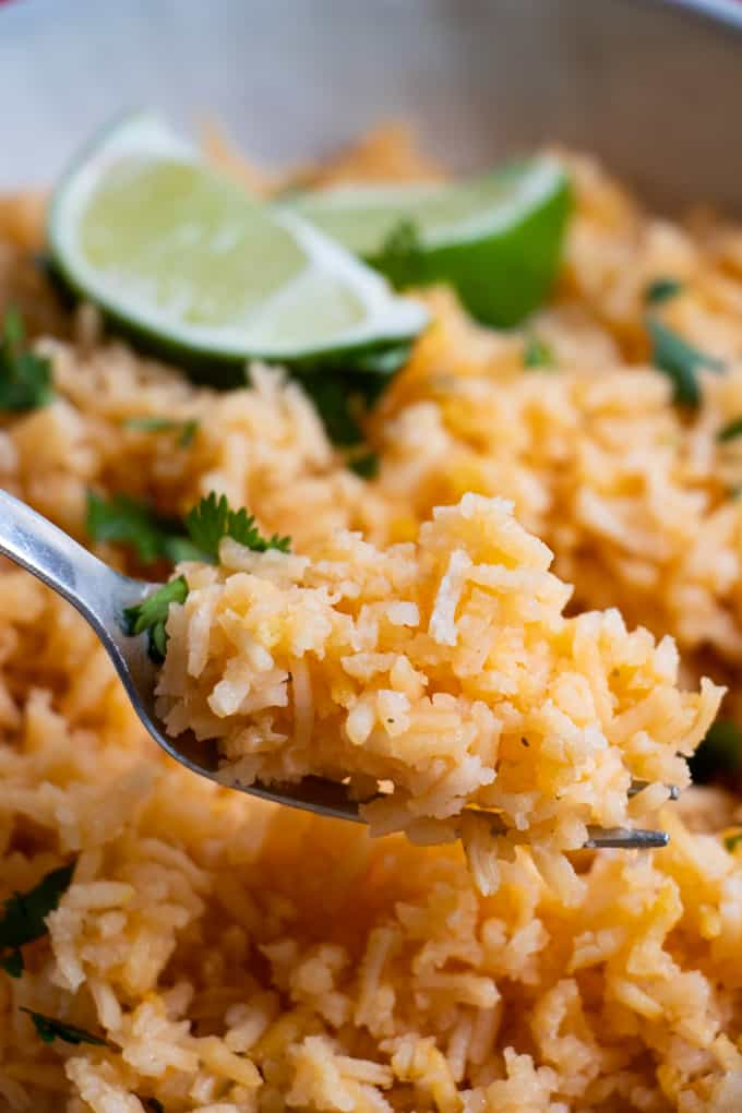 A fork lifting a bite of mexican Spanish rice.