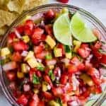 Bowl full of strawberry mango salsa topped with lime wedges.