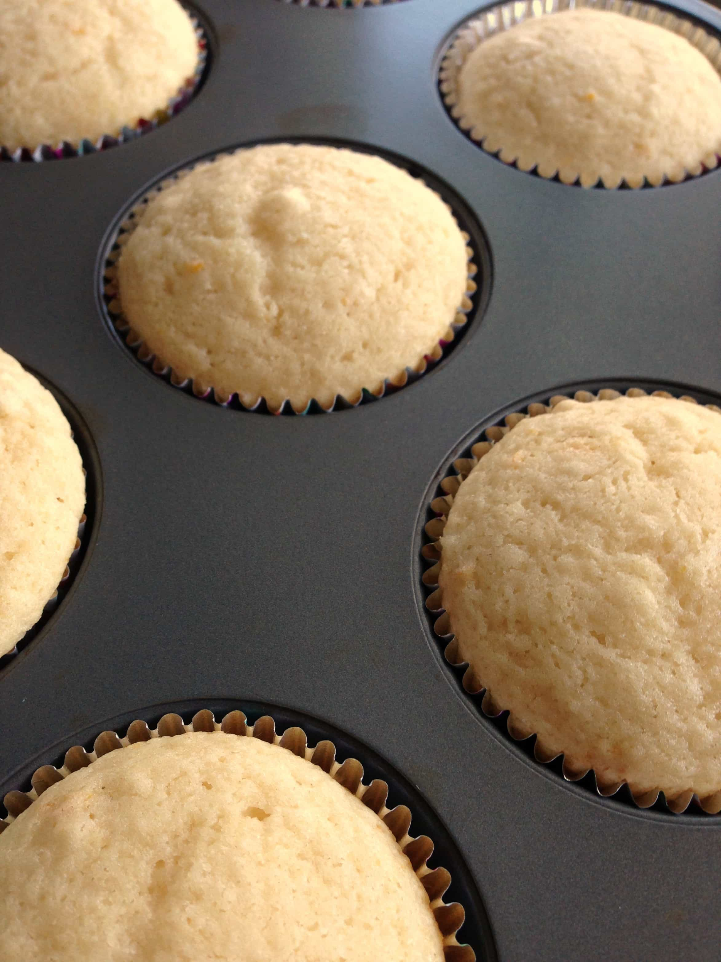Baked lemon cupcakes in a muffin tin.