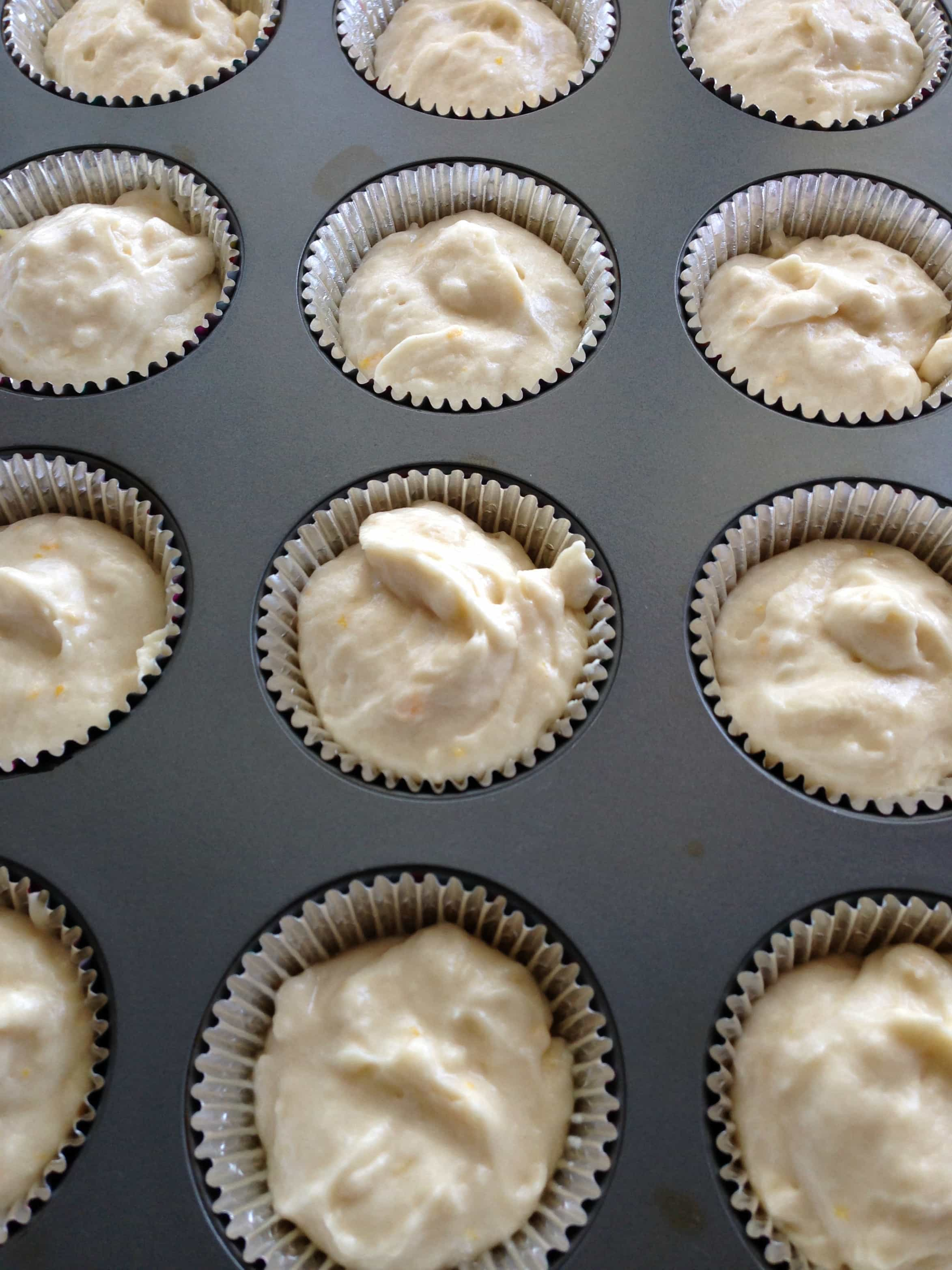 Lemon cupcake batter in cupcake liners in a muffin tin.