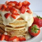 Stack of pancakes topped with cream cheese glaze and cut strawberries.