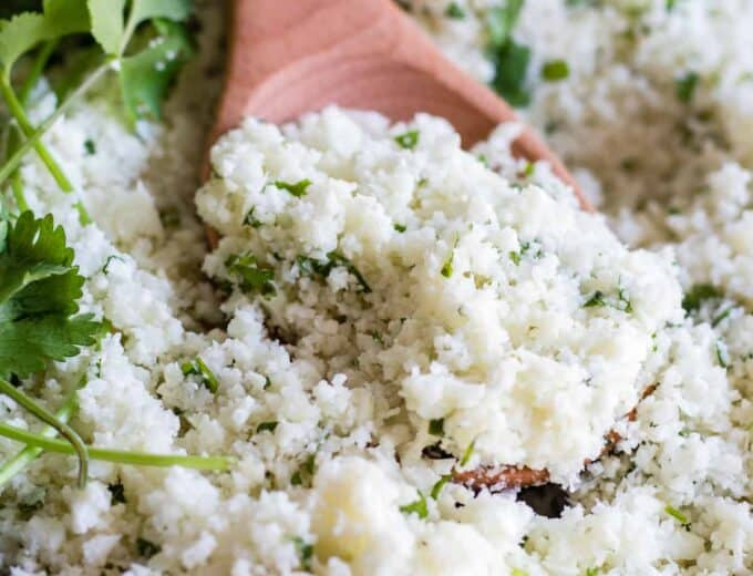 A wooden spoon scooping into a skillet with cilantro lime rice.