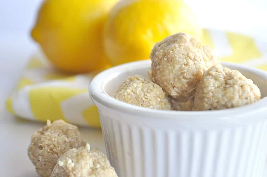 Bowl filled with lemon energy bites with lemons in the background.