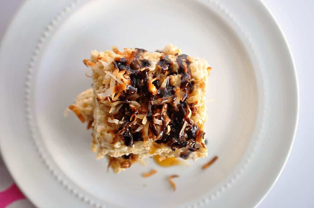 Overhead view of Rice Krispie treats topped with shredded coconut and drizzled with chocolate and caramel.
