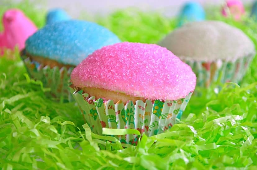 Cupcakes topped with peeps inspired frosting sitting in easter grass.