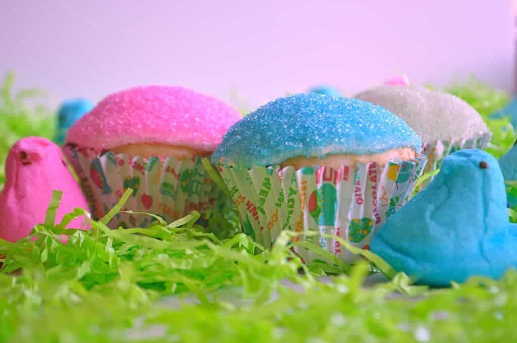 Cupcakes topped with marshmallow frosting dipped in sprinkles set up in green easter grass with marshmallow peeps beside them.