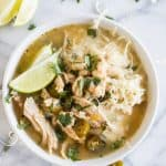 A bowl filled with white chicken chili, topped with cheese, cilantro and lime wedges.