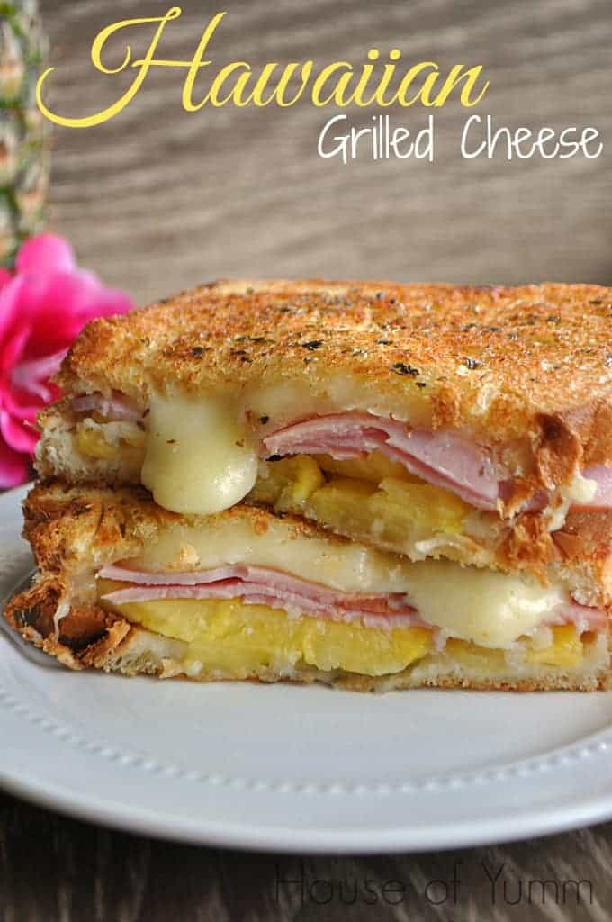 Hawaiian Grilled cheese cut in half and stacked with cheese oozing out of the middle.
