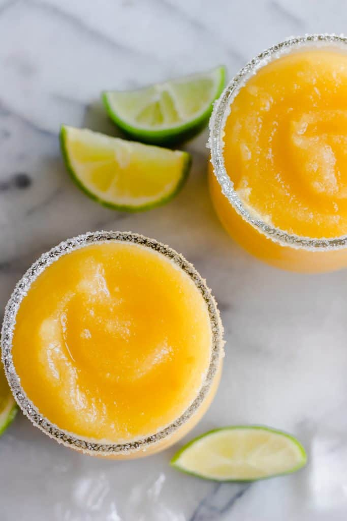 Overhead view of frosty blended mango margarita in a glass rimmed with sugar.