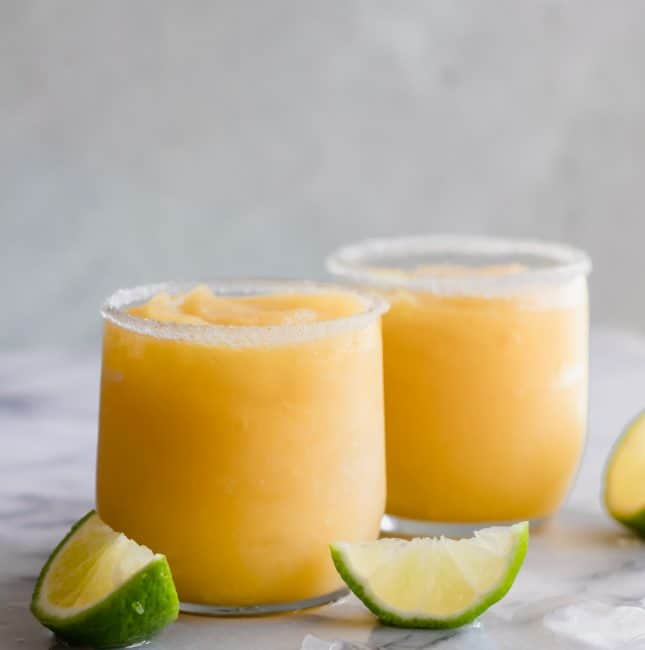 Frosty mango margarita in a glass rimmed with sugar and lime wedges.