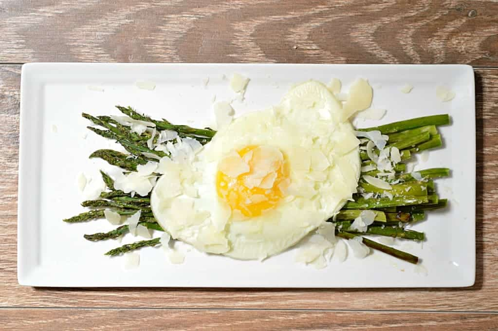 Baked asparagus topped with a sunny side up egg, and shaved parmesan cheese.  This asparagus appetizer could actually be served as an appetizer, a side dish, or even as a lunch meal!   Super easy to make, and DELICIOUS!  This is a dish that is sure to please the whole family!