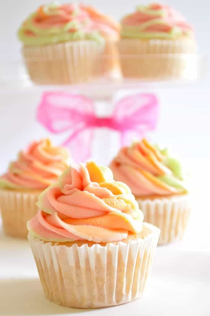 These Rainbow Sherbet Cupcakes are made with real rainbow sherbet in the cake batter and topped with three flavors of swirled frosting! #houseofyummth three flavors of swirled frosting! #houseofyumm