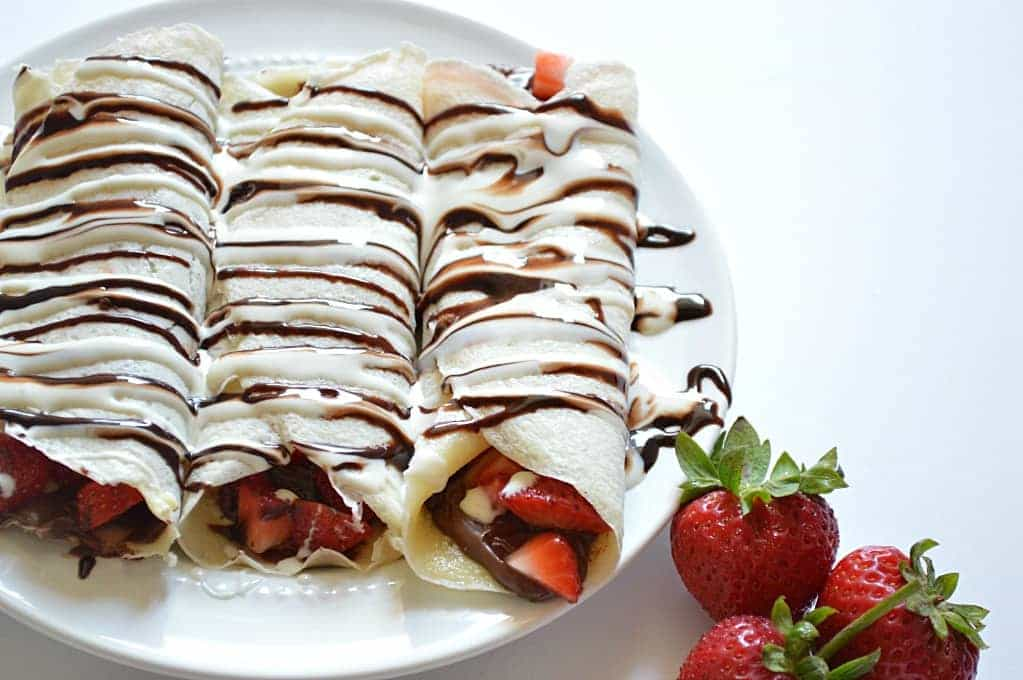 Enjoy S'mores for breakfast with this easily assembled S'mores Crepe recipe!  Crepes filled with Nutella and strawberries and topped with chocolate and marshmallow syrups.  DE-lish!