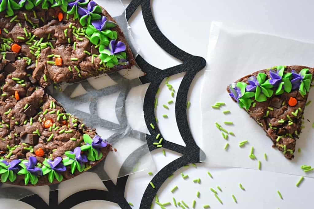 Double Chocolate Fudge Cookie Cake decorated for Halloween with purple and green frosting and pumpkin sprinkles!
