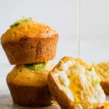 Stacked Jalapeno Cheddar Cornbread muffins, with one cut open and smeared with a sweet honey butter and a honey drizzle running down.