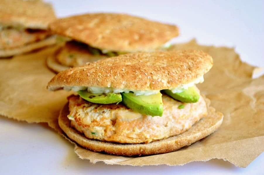 Salmon Burgers topped with avocado and a creamy, refreshing cucumber spread.