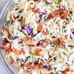 Large glass bowl filled with creamy blue cheese coleslaw topped with bacon.