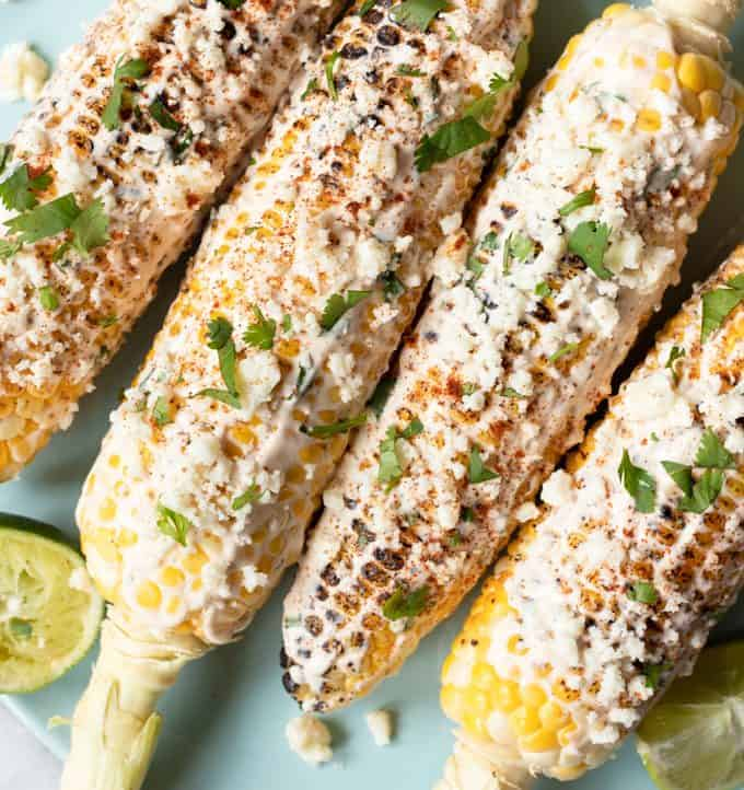 Plated Mexican street corn with lime wedges.