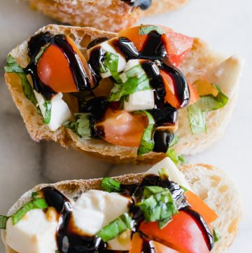 Overhead view of caprese bruschetta drizzled with a balsamic glaze.
