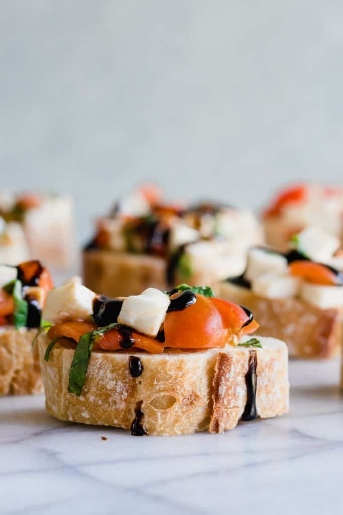 Caprese Bruschetta on top of sliced baguette and drizzled with a balsamic glaze.