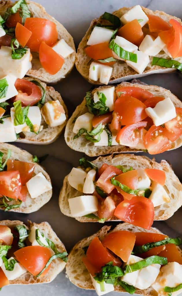 Bread slices laid out and topped with caprese bruschetta, fresh tomatoes, mozzarella and basil.