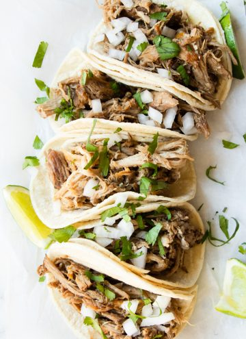 Slow Cooker Pork Carnitas tacos, made on corn tortillas and topped with cilantro and onions.