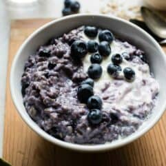 Bowl of blueberry oatmeal topped with creamy vanilla yogurt.