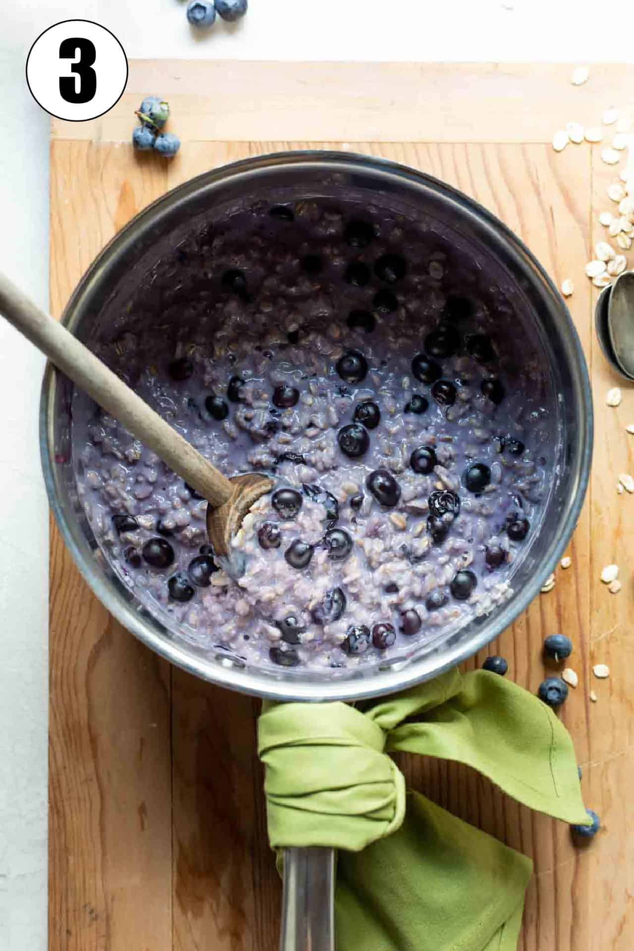 Saucepan filled with cooked, purple colored oatmeal with fresh blueberries.