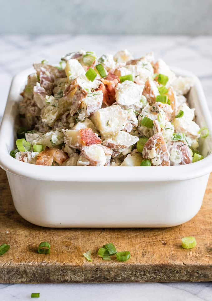 White dish filled with red white and blue potato salad.