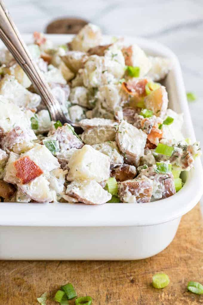 Mixed red white and blue potato salad in a dish being served with a large spoon.