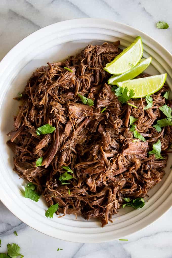 Bowl filled with shredded barbacoa topped with chopped cilantro and lime wedges.