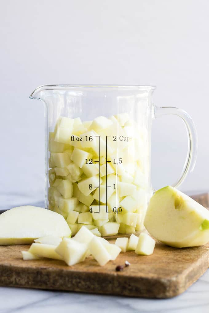 A measuring cup filled with peeled and diced apple for apple bread