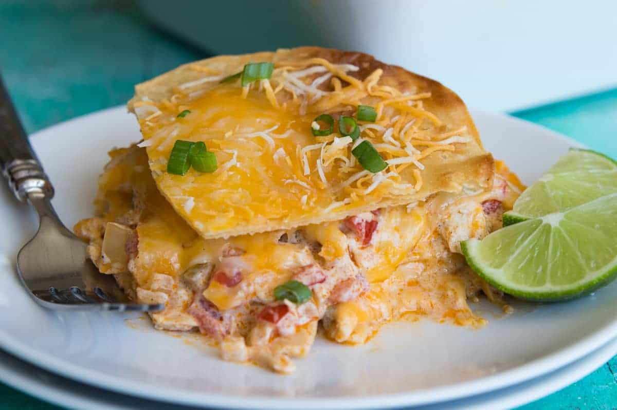 Layers of king ranch chicken dished onto a plate showing melted cheese, layers of tortillas and a creamy chicken mixture with tomatoes, peppers and chiles.