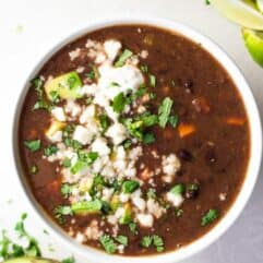 Bowl filled with black bean soup topped with crumbled Queso fresco, cilantro and diced avocado.