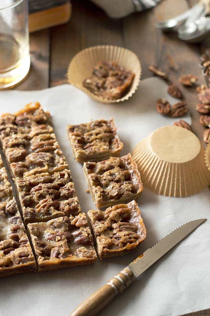Easy to make Boozy Pecan Praline Bars are the perfect sweet treat! Soft, crumbly shortbread with a chewy praline topping!