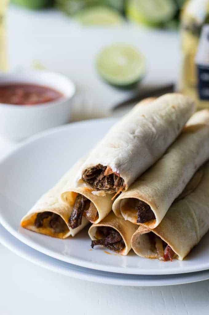 Slow Cooker Steak Fajita Taquitos recipe. Flavorful fajita meat cooked in the slow cooker with peppers and onions then loaded into soft flour tortillas with cheese and baked! These taquitos are snacking perfection!
