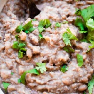 Homemade refried beans served in a large white bowl and topped with diced cilantro.