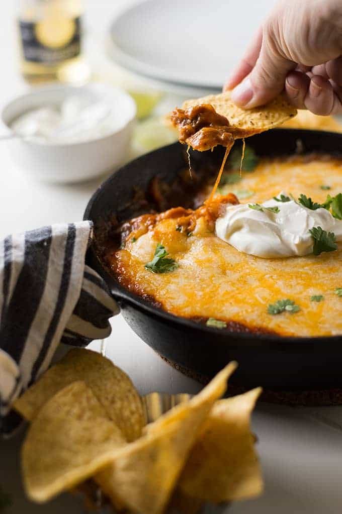 A warm tex mex enchilada dip loaded with ground beef, tons of melty gooey cheese and of course the tex mex chili gravy enchilada sauce. Enjoy the flavors of Texas with this savory snack!