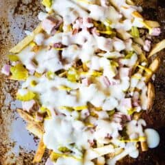 Crispy french fries loaded with all the flavors of a Cuban sandwich and topped with a creamy swiss cheese sauce! The ULTIMATE appetizer or snack recipe! A definite crowd pleaser!