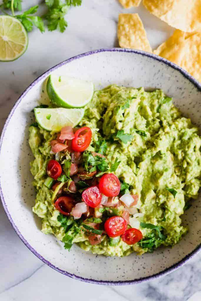 Bowl loaded with guacamole topped with pico de Gallo and limes.