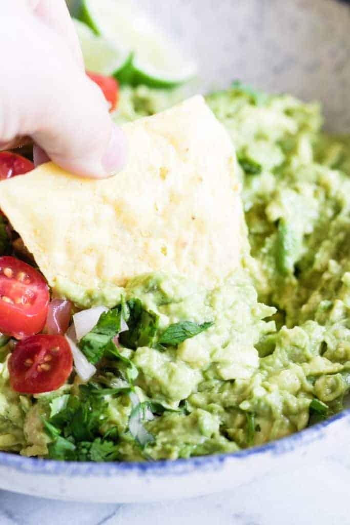 Chip dipping into creamy homemade guacamole.
