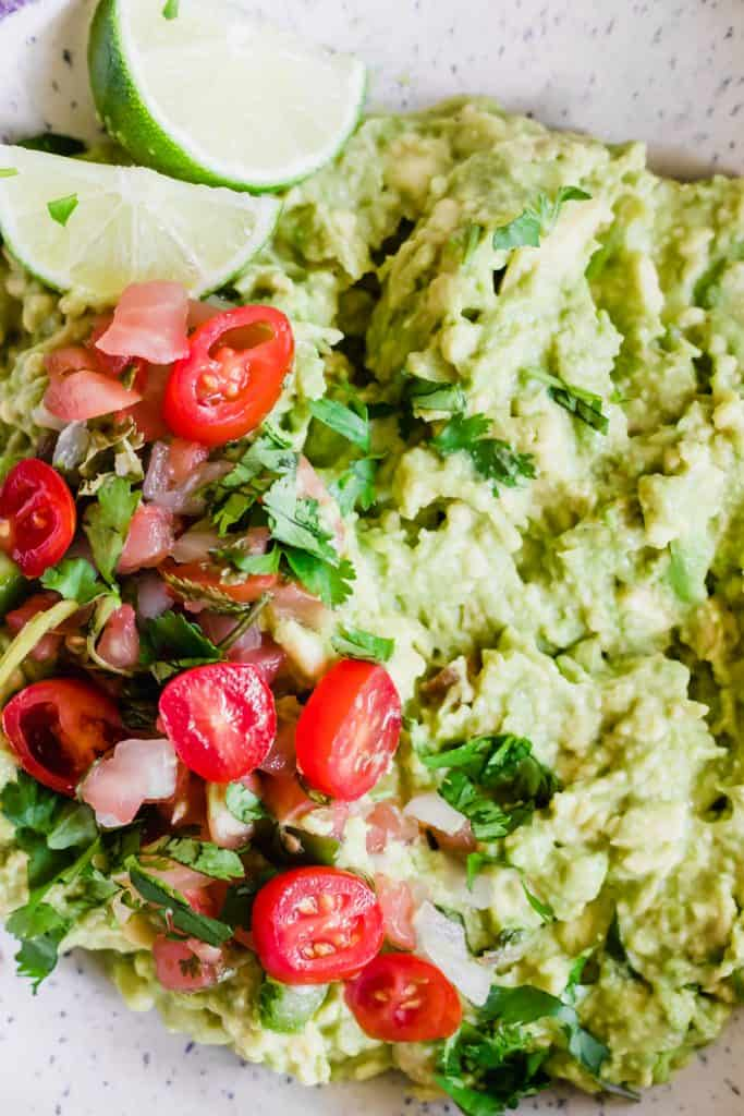 Guacamole topped with tomatoes and cilantro.