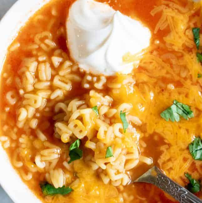 Bowl filled with Mexican Alphabet Soup, sopa de letras, and topped with sour cream, cheese and cilantro.