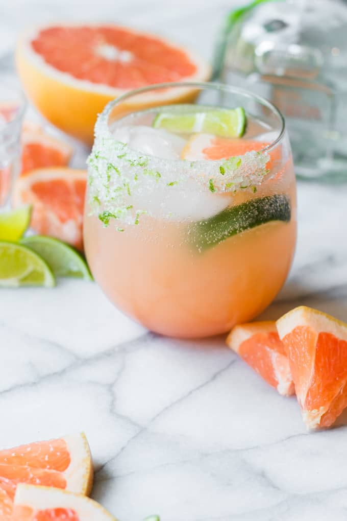 A paloma cocktail on a marble background surrounded by wedges of lime and grapefruit.