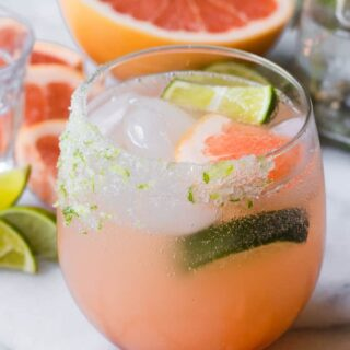 Grapefruit Paloma in a glass garnished with lime and grapefruit wedges.
