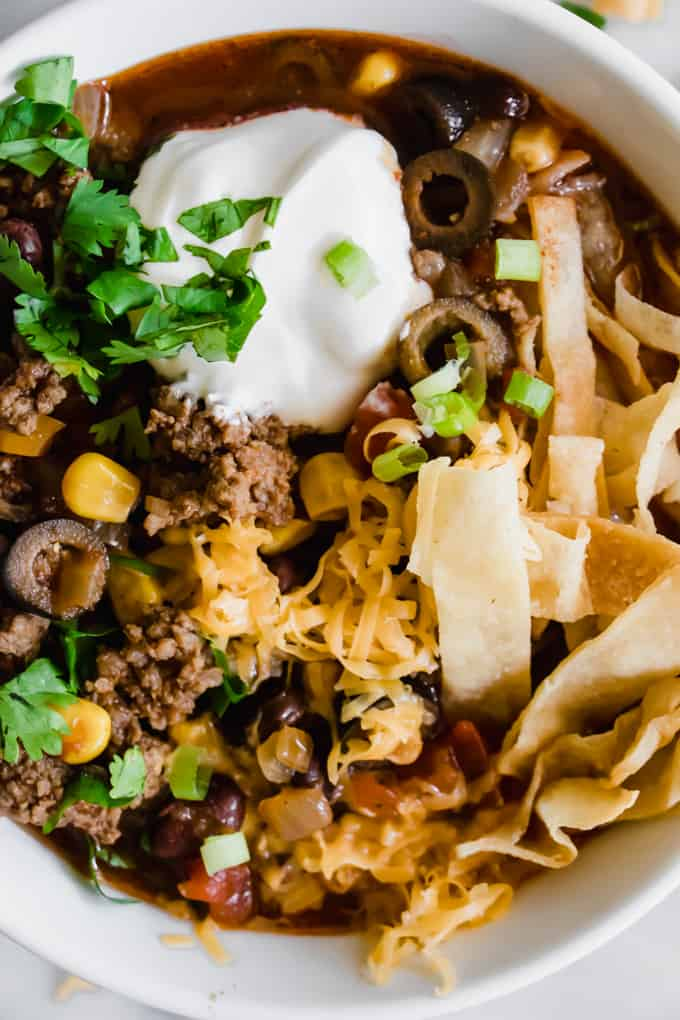 Close up image of easy taco soup showing ground beef, olives, corn, tomatoes, and a dark red broth.